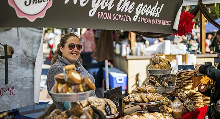 woman with display of baked goods at sarasota farmers market